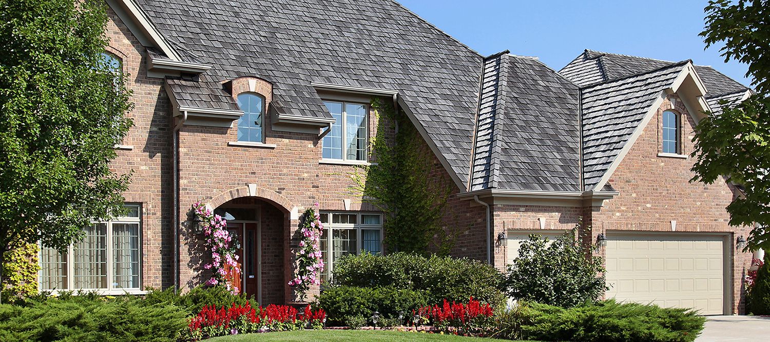 Exterior of a large suburban brick home during a home inspection
